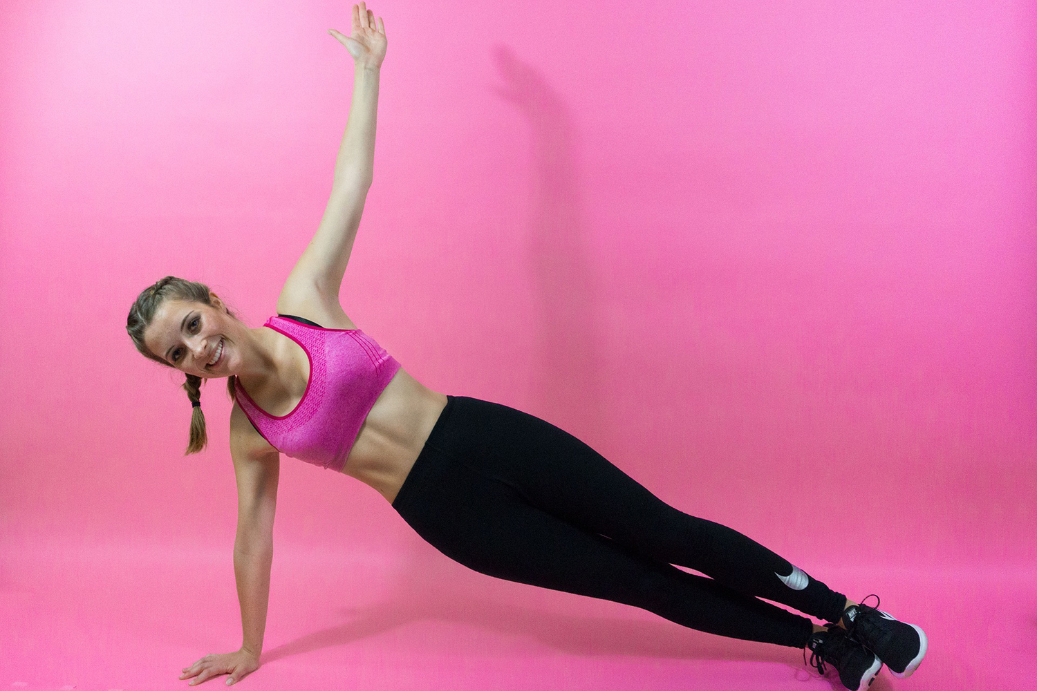 Athletic Woman Doing Side Plank With On Arm Raised