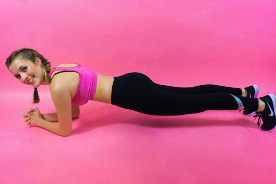 Smiling Woman Doing Front Plank Exercise