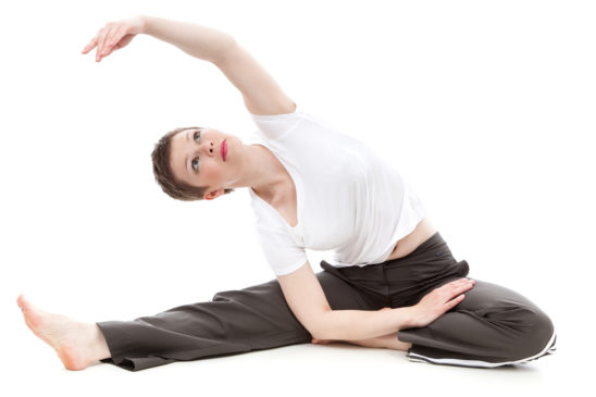 Fitness Woman Stretching While Sitting