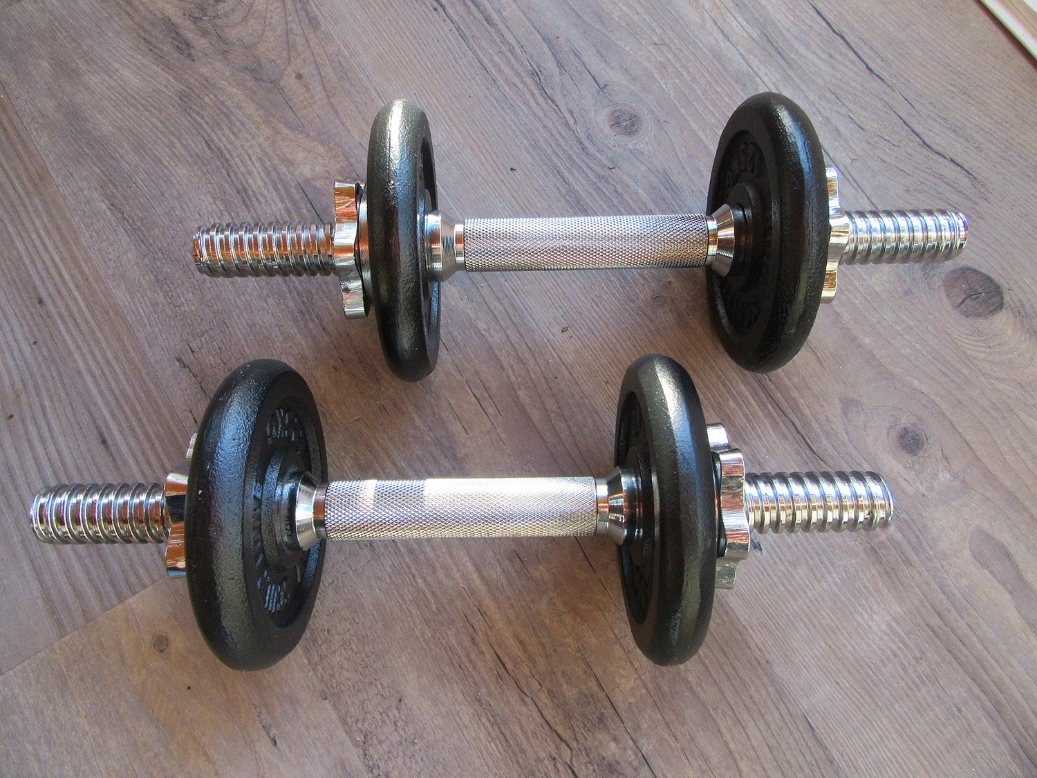 A Pair of Dumbbells Placed on Wooden Floor