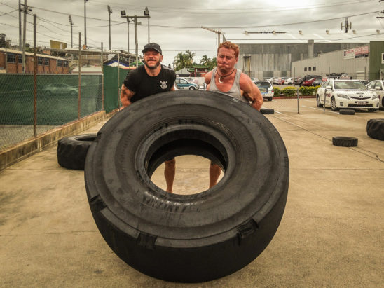Crossfit Men Doing Tyre Flipping Exercise