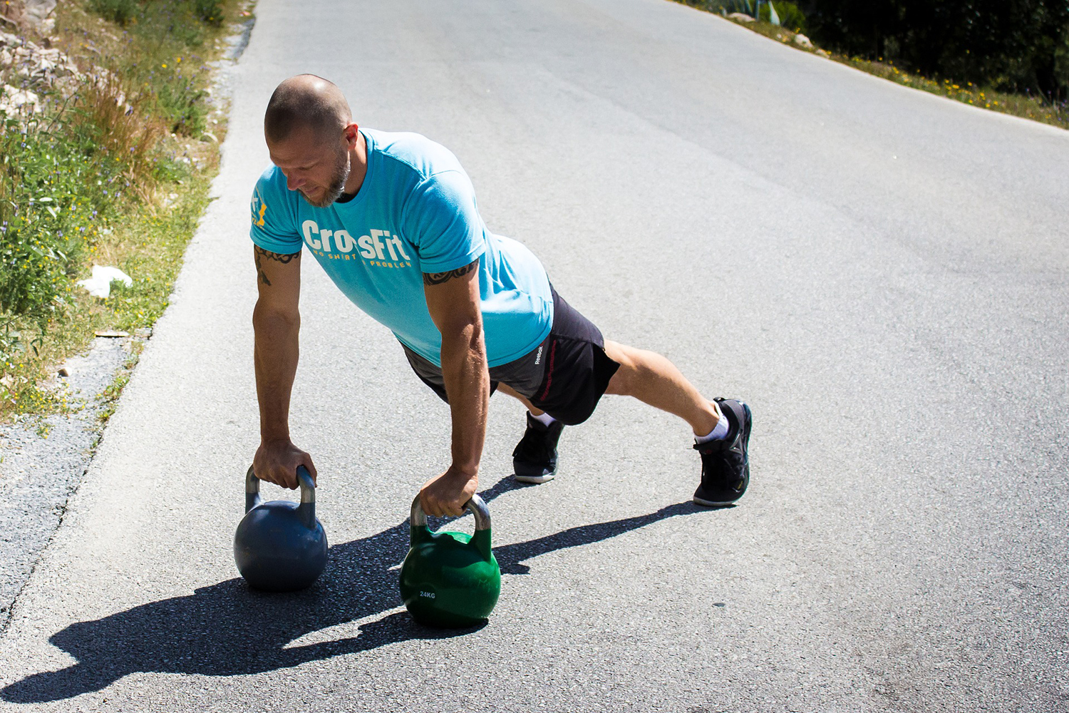Crossfit Man Exercising With Kettlebells Outdoors