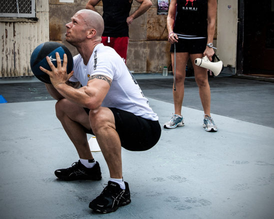 Fit Man Exercising With Medicine Ball. Trainer Instructing Fit Man