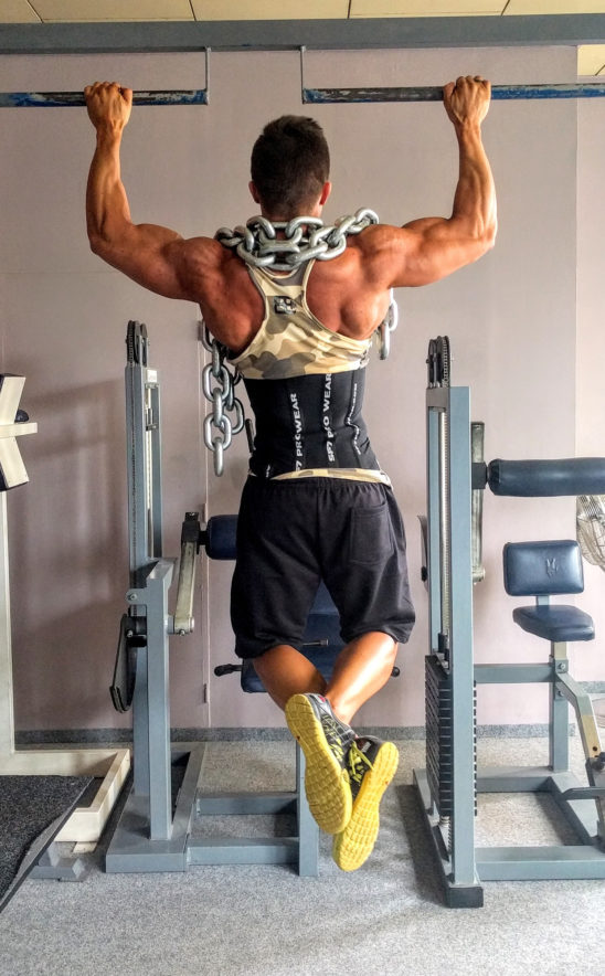 Muscular Man Doing Weighted Pull Ups Exercise
