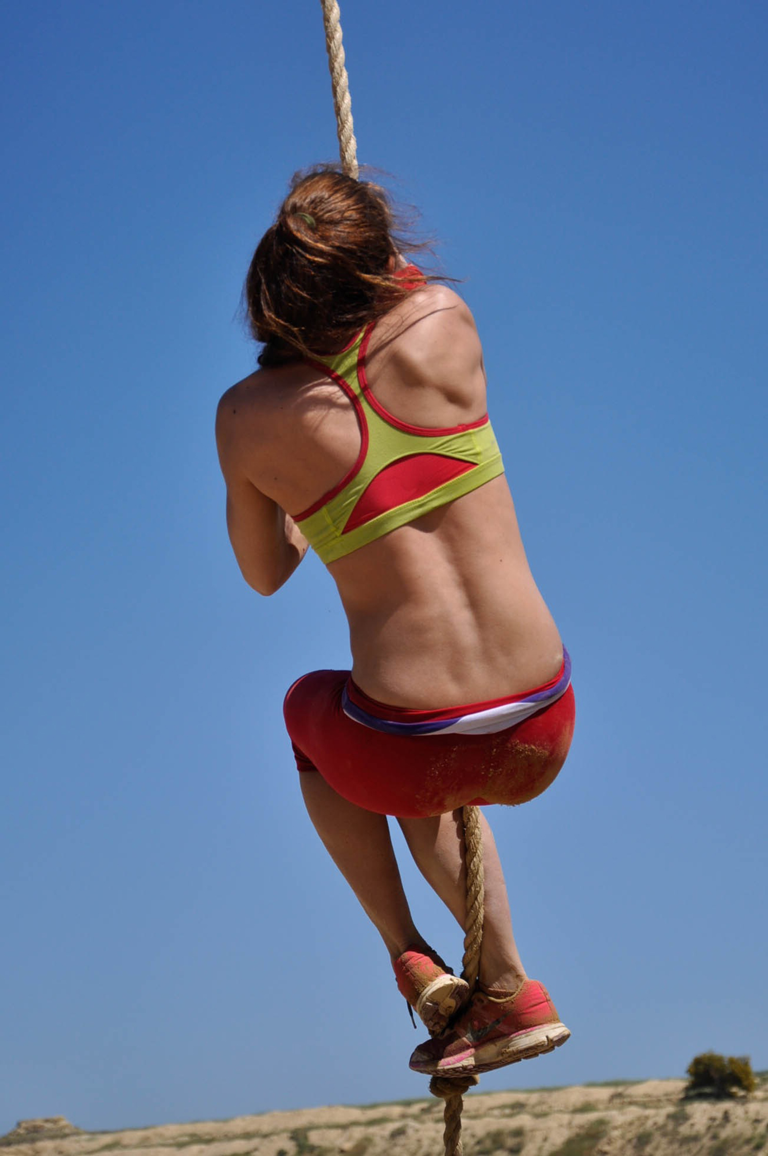 Strong Woman Rope Climbing on A Sunny Day. Woman Doing Rope Exercise Outdoors