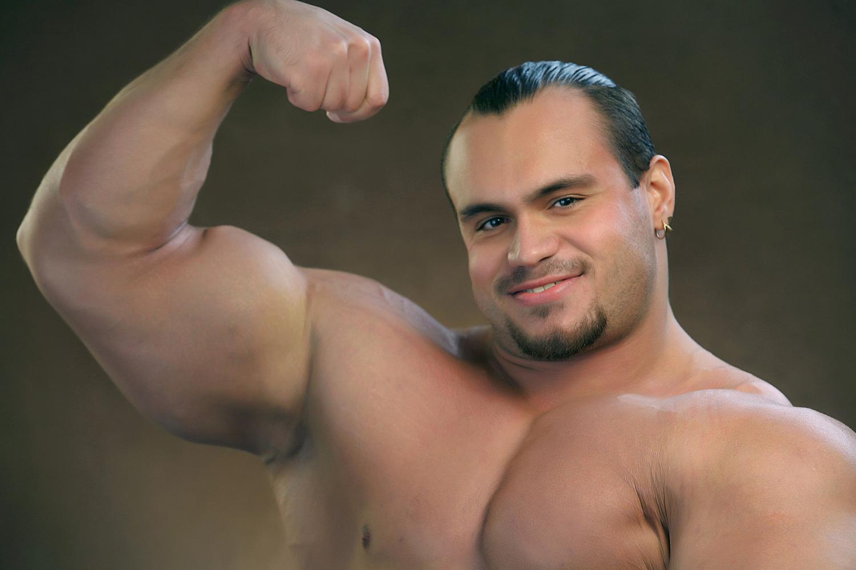 Male Bodybuilder Flexing Biceps Muscles