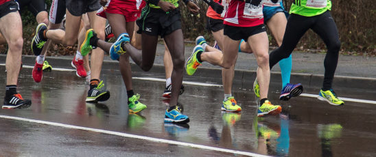 Athletes Running In the Rain. Marathon Competition on Rainy Day