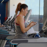 Fit Woman Chatting on The Phone While Exercising on The Treadmill