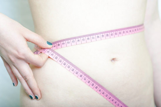 Woman Measuring Waist Size With Tape Measure