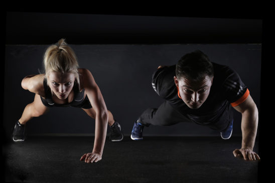 Fitness Couple Doing One Arm Push Ups