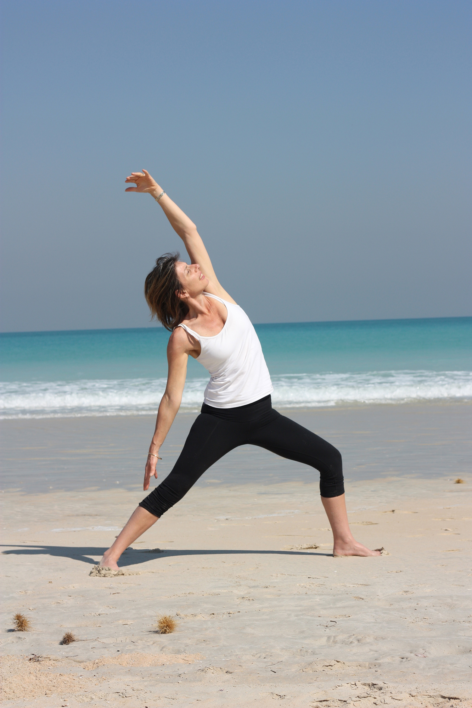 Fitness Woman Practicing Yoga at The Beach