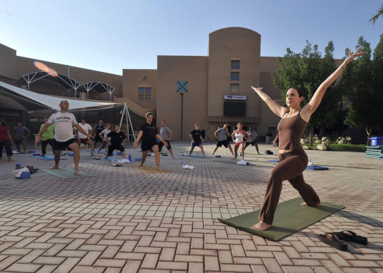 Men and Women In Outdoor Yoga Class