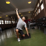Strong Man Lifting Kettlebells While Kneeling