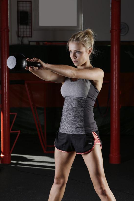 Athletic Woman Doing Kettlebell Swings