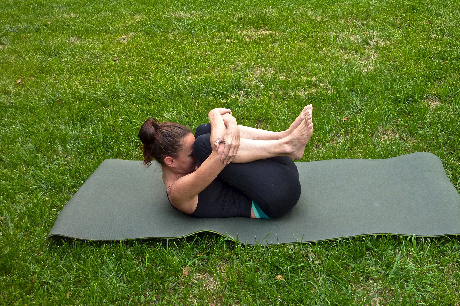 Flexible Woman Doing Knee To Chest Stretch Outside