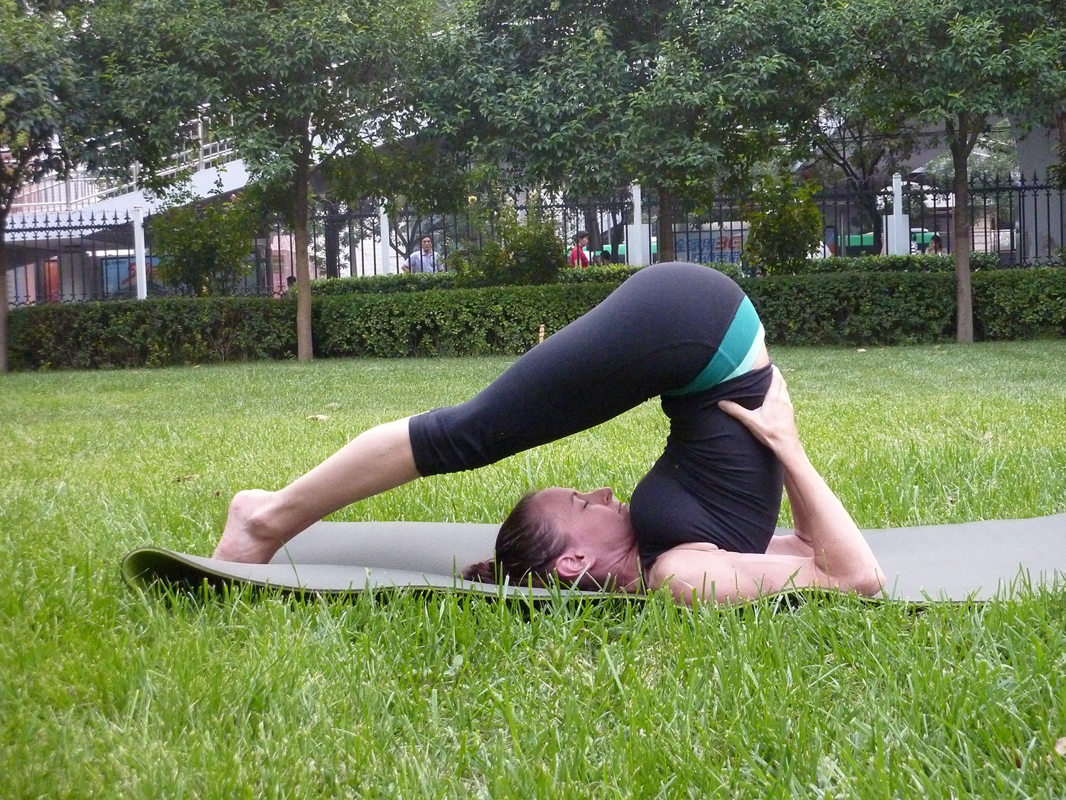 Flexible Woman Doing Plow Pose Outdoors
