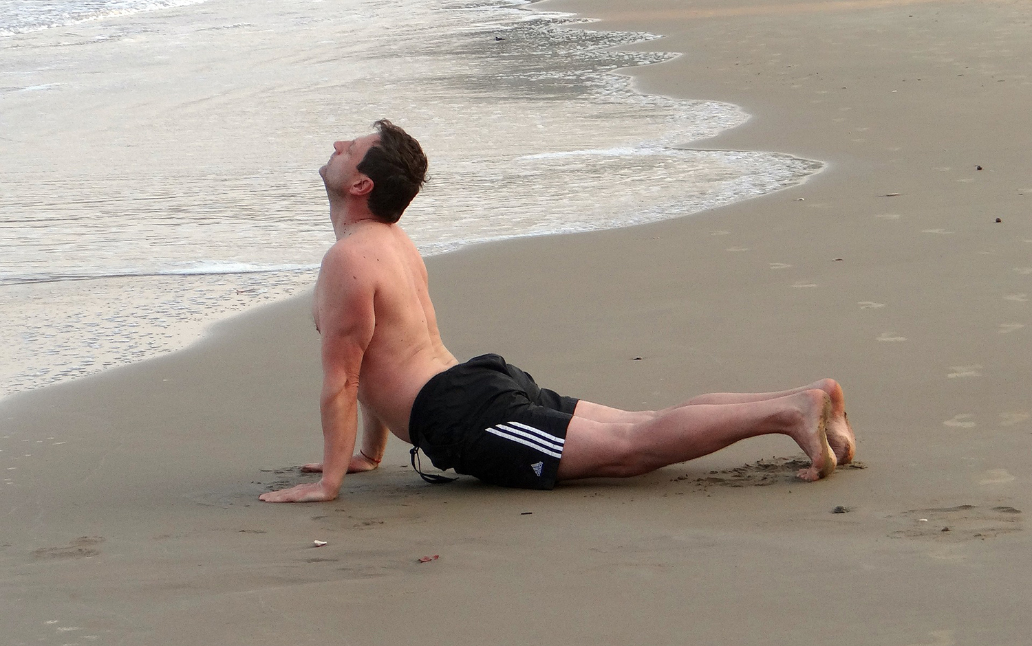Man Doing Cobra Pose At The Beach