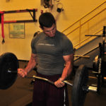 Muscular Man Doing Barbell Curls Exercise