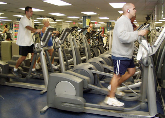 Man Doing Cardio on Elliptical Machine In The Gym