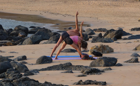 Fit Couple Practicing Yoga At The Beach