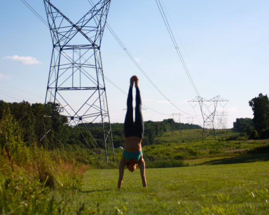 Woman Doing Handstand on Grass
