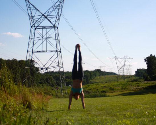 Woman Doing Handstand on Grass