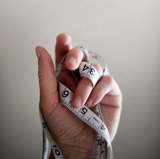 Hand Holding Tape Measure, Weight Loss Concept