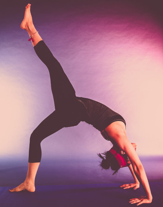 Woman Doing Back Bridge Pose With One Leg Raised