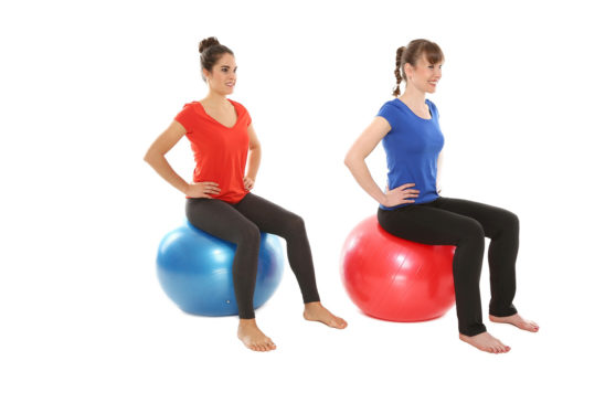 Two Fit Women Sitting on Swiss Ball