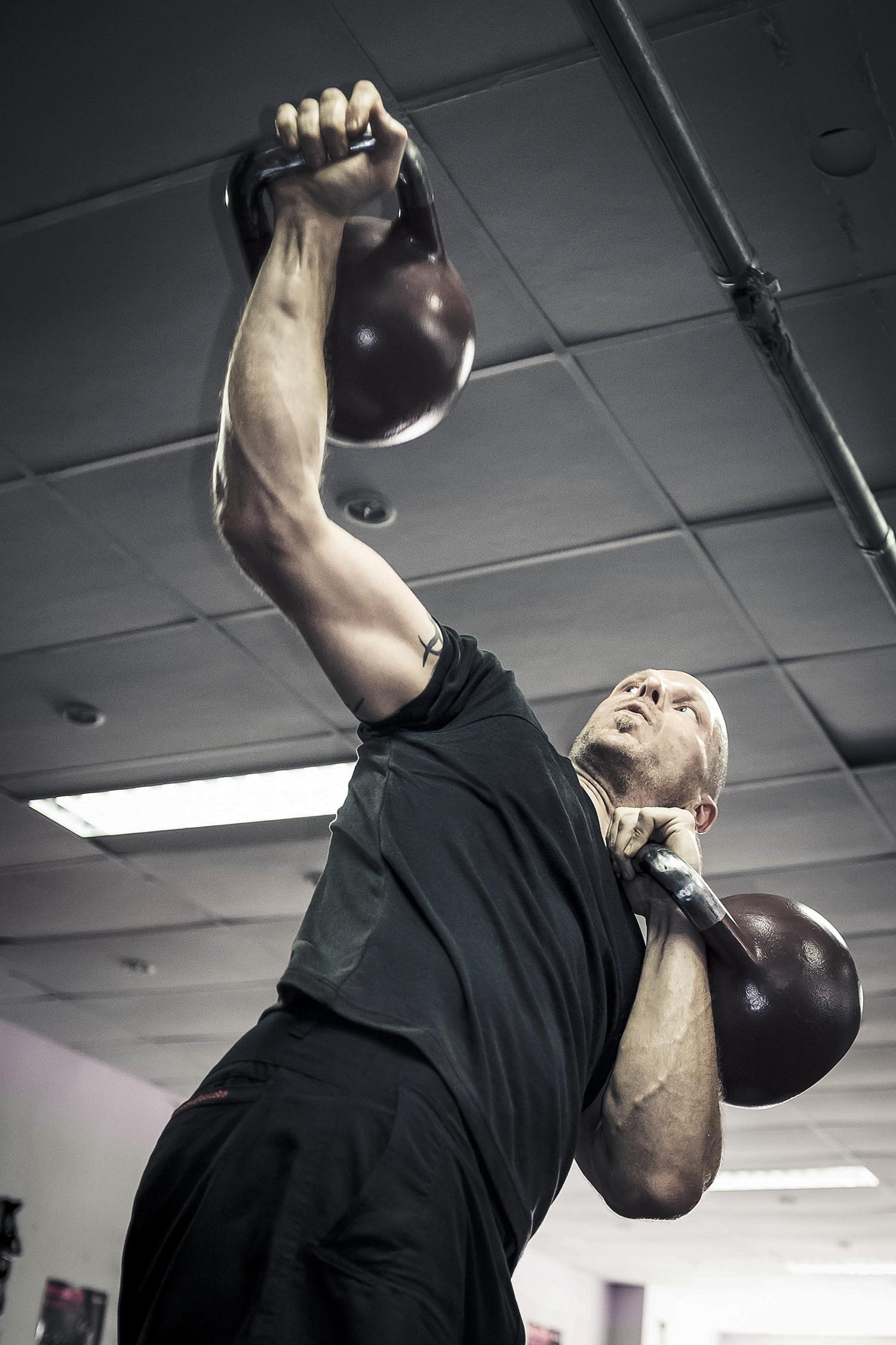 Strong Man Lifting Kettlebells