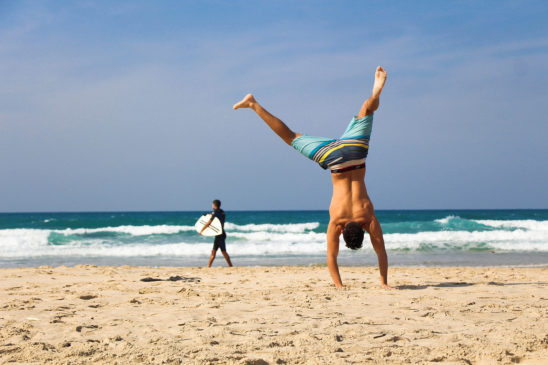Fitness Man Doing Handstand At The Beach