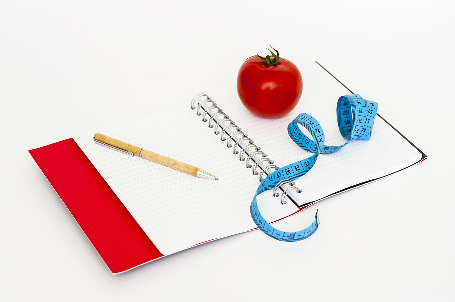 Weight Loss and Dieting Concept. Tape Measure, Tomato, Pen, and Paper
