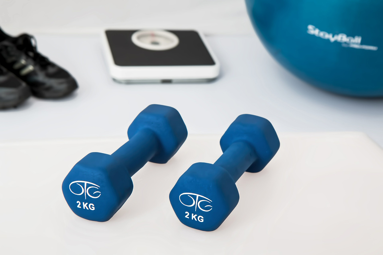 Fitness and Weight Loss Concept. Sports Shoes, Dumbbells, Weight Scale and Swiss Ball