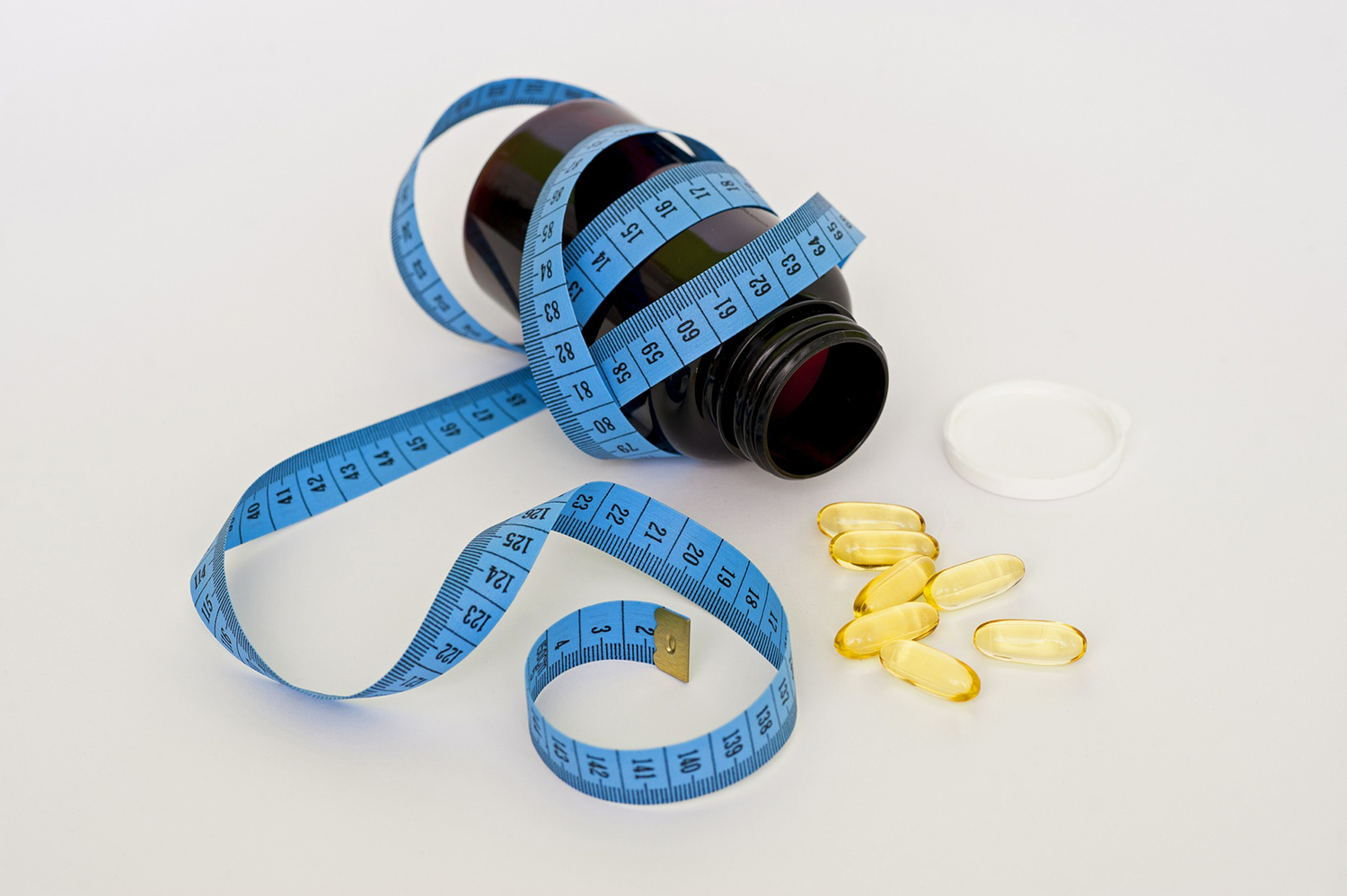Weight Loss Pills Concept. Tape Measure and Pills