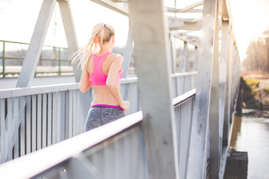 Healthy Woman Running Across Bridge During Morning Run