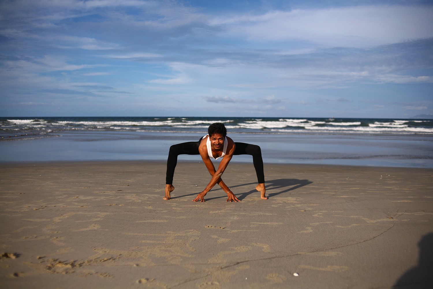 Flexible Man Practicing Yoga Bending in Variation of Goddess or Sumo Squat Pose