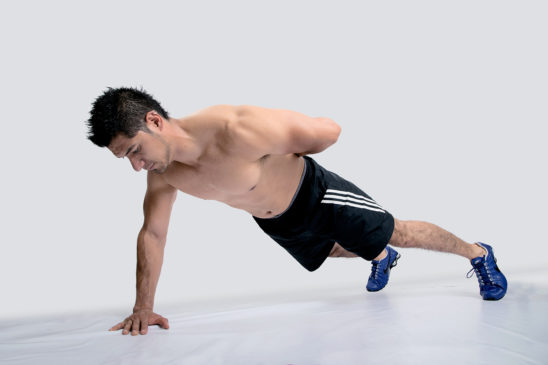 Athletic Man Doing One Arm Push Ups