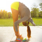 Fit Woman Bending Forward To Stretch Legs and Back