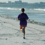 Fit Woman Running at The Beach
