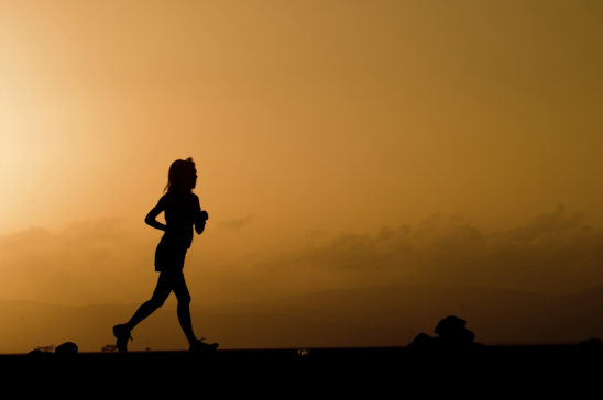Silhouettes of Runner Running In The Evening