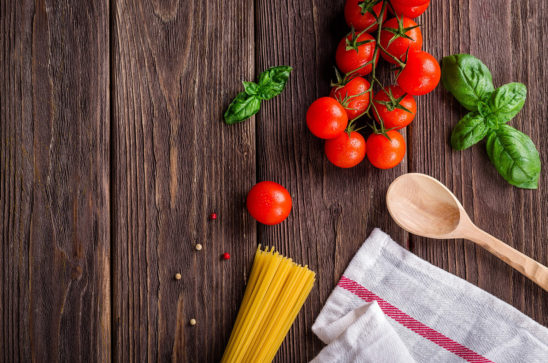 Tomatoes and Pasta On Kitchen Wooden Table