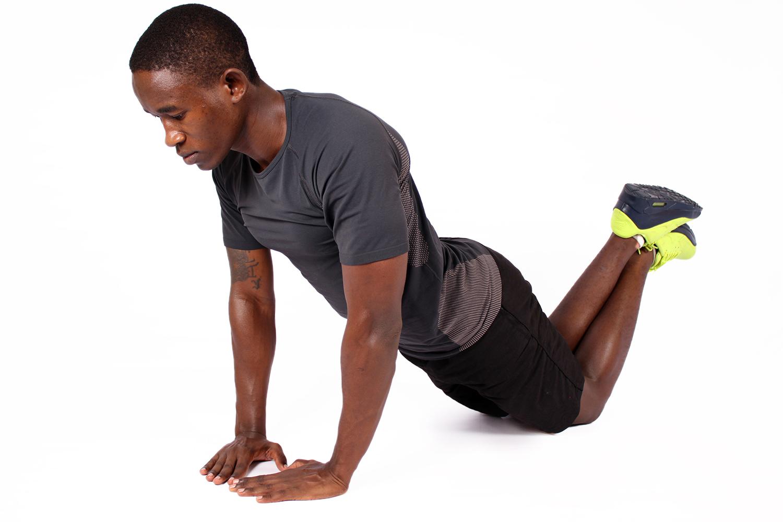 African man doing diamond push ups on his knees