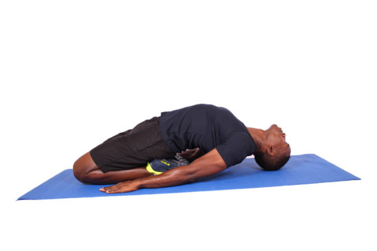 African man doing hips and spinal stretch on yoga mat