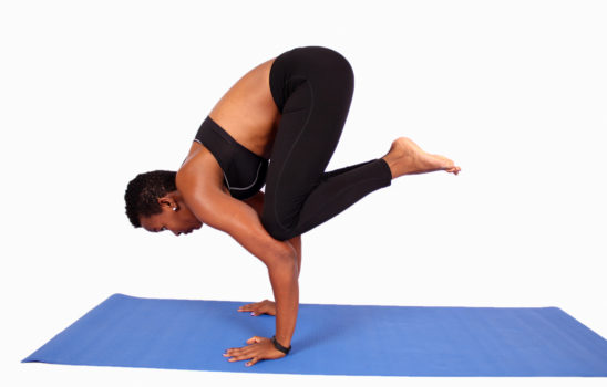 African woman doing beginner handstand yoga pose
