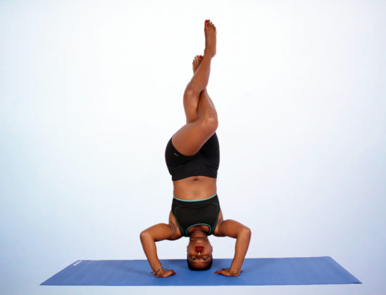 Yogi Doing Eagle Legs in Headstand Yoga Pose