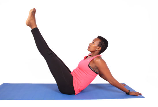African Woman Doing V Ups Ab Exercise With Hand On The Floor