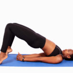 African woman doing yoga hips raised