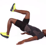 Athletic african male legs raised doing butt exercise