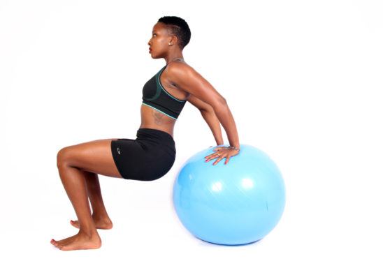 Athletic african woman doing triceps dips on swiss ball