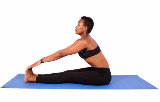 Athletic african woman touching toes stretching